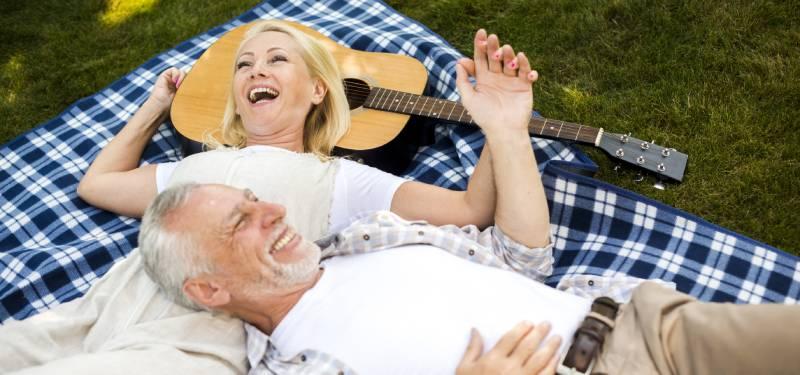 Stariji bračni par na pikniku kako leže na travi pored gitare