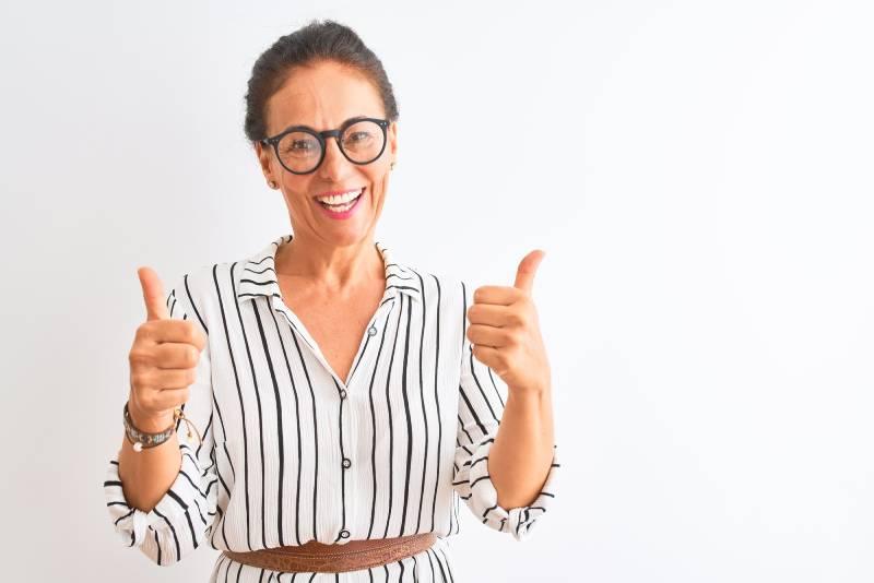 Žena sa naočarima koja se smeje i sa obe ruke pokazuje thumbs up