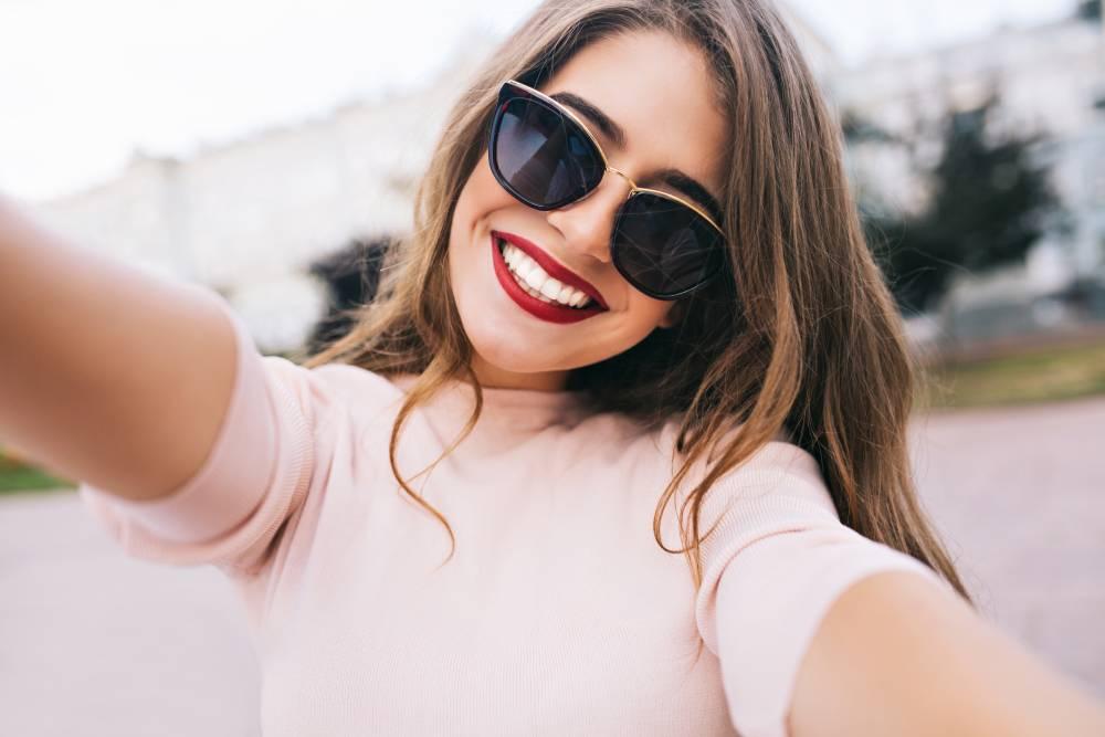 Slika nasmejane devojke sa crvenim karminom i naočarima za sunce