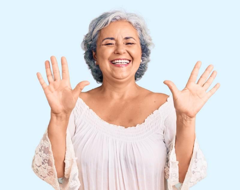 Slika starije gospođe koja se smeje i drži podignute ruke u visini glave