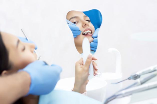 Devojka na pregledu kod zubara i drži ogledalo u ruci