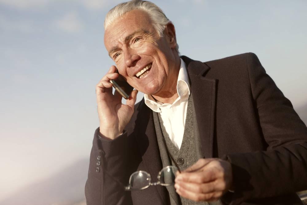 Slika starijeg čoveka kako se smeje dok priča na telefon