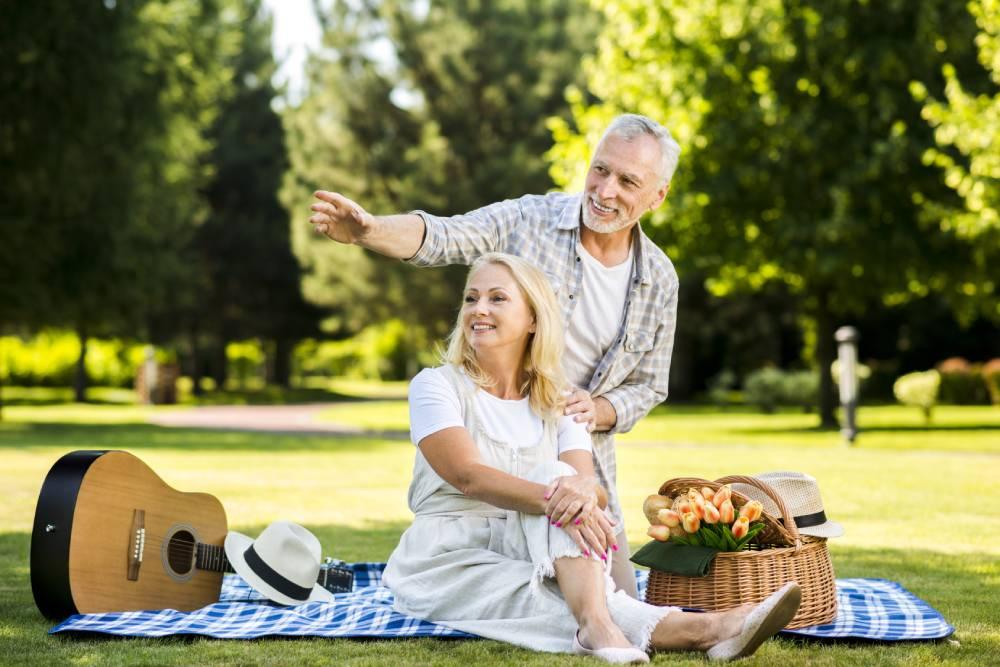 Stariji bračni par na pikniku u parku dok sede na đebetu sa giratom i korpom pored njih