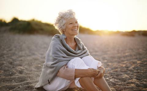 Starija žena sedi na pesku i nasmejana gleda zalazak sunca