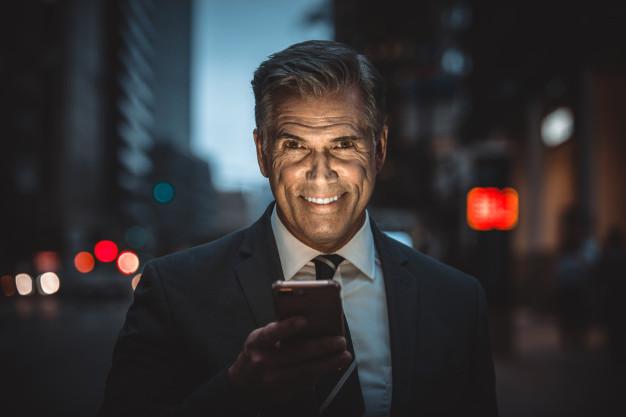 Čovek u srednjim godinama koji se smeje i u rukama drži telefon