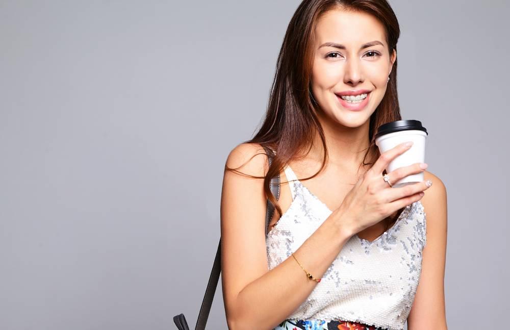 Devojka sa fiksnom protezom koja se smeje i drži kafu za poneti u ruci