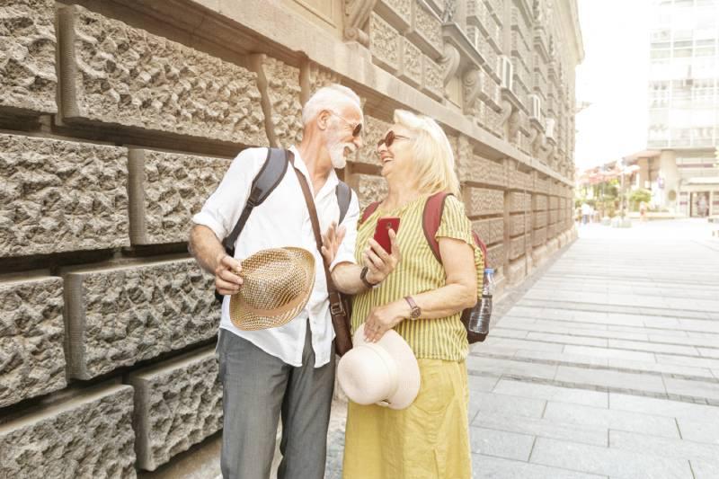 Stariji bračni par koji se gleda i smeje na ulicama Beograda