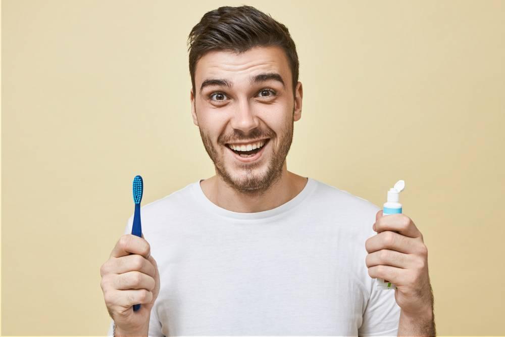 Nasmejan momak koji drži pastu za zube i četkicu jer ne želi da dobije karijes