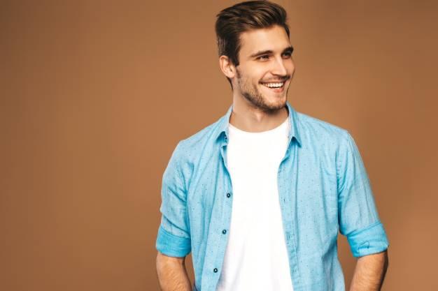 Dečko u plavoj košulji koji se smeje nakon uklanjanja kamenca sa zuba