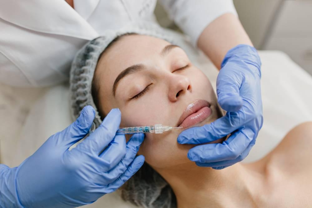 Devojka na tretmanu povećanja usana hijaluronskim filerom prima vakcinu