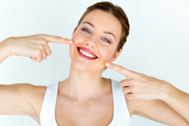 Žena koja se smeje i pokazuje na svoje nove implante
