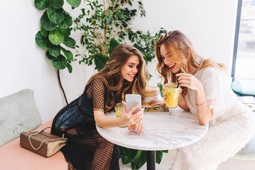 Dve-devojke-dugackih-kosa-sede-i-gledaju-telefon-smejuci-se