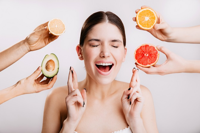 Joyful girl makes wish. Portrait of model without makeup on white background with fruits